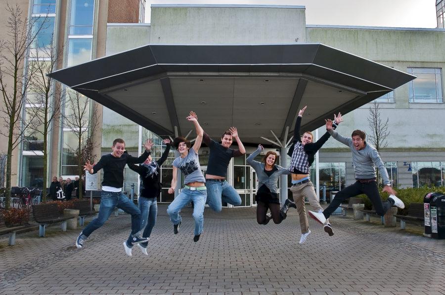 Ett gäng studenter utanför entrén till Campus