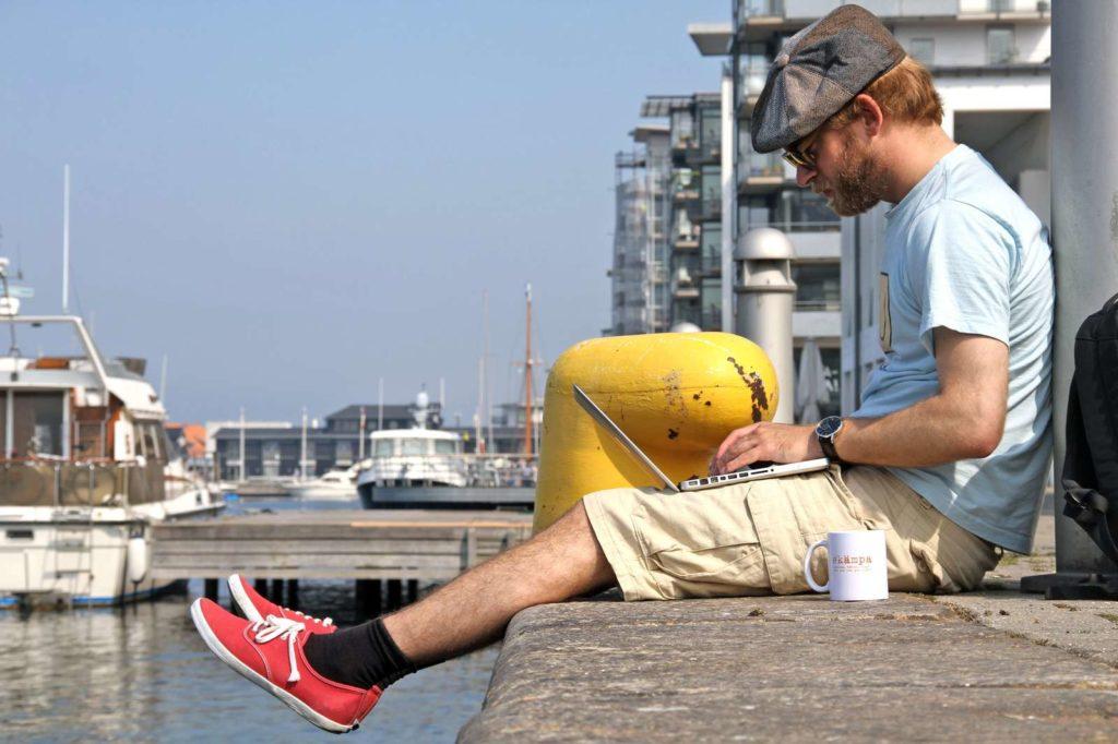 Student skriver på sin uppsats vid vattnet